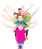 Group of smiling children with raised hands. Group of smiling children with raised hands in colorful t-shirts standing together. Top view. Isolated on white royalty free stock image