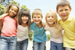 Group Of Smiling Children Relaxing In Park Stock Image