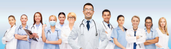 Group of smiling doctors with clipboard over gray Stock Photos
