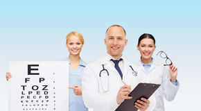 Group of smiling doctors with eye chart Stock Photography