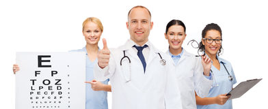 Group of smiling doctors with eye chart Royalty Free Stock Images