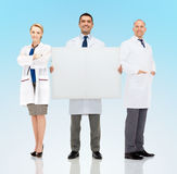 Group of smiling doctors holding white blank board Royalty Free Stock Photography