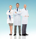 Group of smiling doctors in white coats. Healthcare, advertisement, people and medicine concept - group of smiling doctors in white coats over blue background stock photos