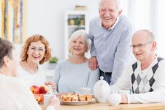 Elderly people at retirement home. Group of smiling elderly people sitting at table with tea and cake, telling jokes and relaxing at retirement home for seniors stock images