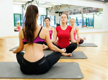 Group of smiling feamle meditating in the gym Stock Images