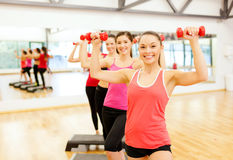 Group of smiling female with dumbbells and step Stock Image
