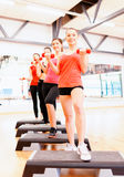 Group of smiling female with dumbbells and step Stock Images