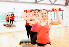 Group of smiling female with dumbbells and step Royalty Free Stock Photography