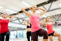 Group of smiling femalewith trainer exercising Stock Photos