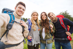 Group of smiling friends with backpacks hiking. Adventure, travel, tourism, hike and people concept - group of smiling friends with backpacks making selfie Royalty Free Stock Photography