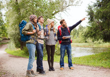 Group of smiling friends with backpacks hiking. Adventure, travel, tourism, hike and people concept - group of smiling friends with backpacks and map outdoors Stock Image