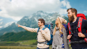 Group of smiling friends with backpacks hiking. Adventure, travel, tourism, hike and people concept - group of smiling friends with backpacks pointing finger Royalty Free Stock Photo