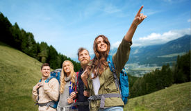 Group of smiling friends with backpacks hiking. Adventure, travel, tourism, hike and people concept - group of smiling friends with backpacks pointing finger Stock Photo