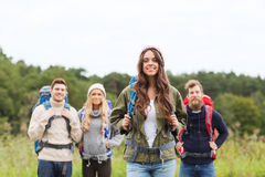 Group of smiling friends with backpacks hiking. Adventure, travel, tourism, hike and people concept - group of smiling friends standing with backpacks Royalty Free Stock Image