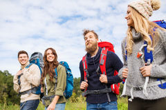 Group of smiling friends with backpacks hiking. Adventure, travel, tourism, hike and people concept - group of smiling friends walking with backpacks Stock Photo