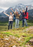 Group of smiling friends with backpacks hiking. Travel, tourism, hike, gesture and people concept - group of smiling friends with backpacks raising hands over royalty free stock image