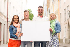 Group of smiling friends with blank white board. Travel, vacation and advertising concept - group of smiling friends with blank white board in the city Royalty Free Stock Images