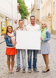 Group of smiling friends with blank white board Stock Image