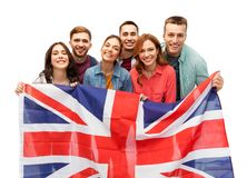 Group of smiling friends with british flag. Patriotism, citizenship and friendship concept - group of smiling friends with british flag over white background royalty free stock photos