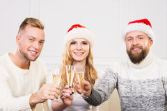 Group of smiling friends in Christmas hats celebrating Royalty Free Stock Image