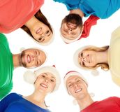 Group of smiling friends in Christmas hats embracing together. Royalty Free Stock Image