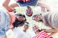 Group of smiling friends in circle - bottom view. Group of smiling friends embraced in circle - bottom view royalty free stock photos