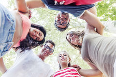 Group of smiling friends in circle - bottom view. Group of smiling friends embraced in circle - bottom view stock photo