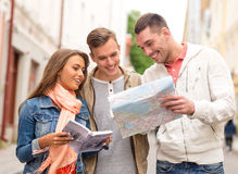Group of smiling friends with city guide and map stock photography