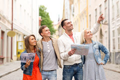 Group of smiling friends with city guide and map Royalty Free Stock Image