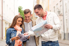 Group of smiling friends with city guide and map Royalty Free Stock Photos
