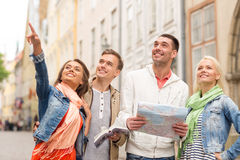 Group of smiling friends with city guide and map Stock Image