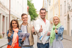 Group of smiling friends with city guide and map Royalty Free Stock Images