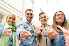 Group of smiling friends in city pointing finger Royalty Free Stock Photos