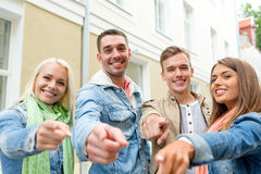 Group of smiling friends in city pointing finger Stock Photography