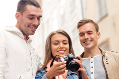 Group of smiling friends with digital photocamera Royalty Free Stock Image