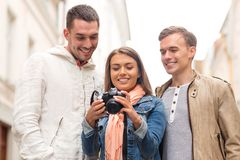 Group of smiling friends with digital photocamera Stock Photo
