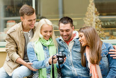 Group of smiling friends with digital photocamera Stock Photos