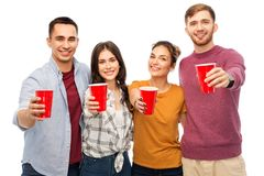 Group of smiling friends with drinks in party cups royalty free stock photos