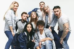 Group of smiling friends in fashionable jeans. The young men and women posing at studio. The fashion, people, happy, lifestyle, clothes concept stock photos