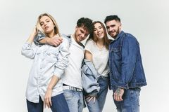 Group of smiling friends in fashionable jeans. The young men and women posing at studio. The fashion, people, happy, lifestyle, clothes concept royalty free stock images