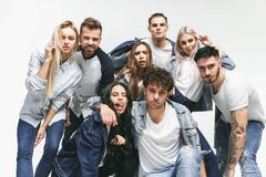 Group of smiling friends in fashionable jeans. The young men and women posing at studio. The fashion, people, happy, lifestyle, clothes concept royalty free stock photography