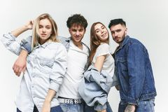 Group of smiling friends in fashionable jeans. The young men and women posing at studio. The fashion, people, happy, lifestyle, clothes concept royalty free stock photo