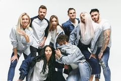 Group of smiling friends in fashionable jeans. The young men and women posing at studio. The fashion, people, happy, lifestyle, clothes concept royalty free stock photos