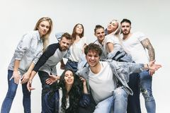 Group of smiling friends in fashionable jeans. The young men and women posing at studio. The fashion, people, happy, lifestyle, clothes concept stock images