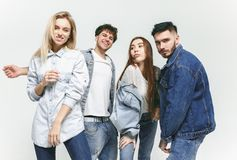 Group of smiling friends in fashionable jeans. The young men and women posing at studio. The fashion, people, happy, lifestyle, clothes concept stock photo
