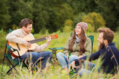 Group of smiling friends with guitar outdoors Stock Images