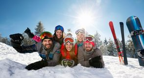 Smiling friends having fun on ski holiday in mountains. Group of smiling friends having fun on ski holiday in mountains royalty free stock image