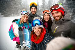 Group of smiling friends having fun Snowboarders and skiers maki. Group of smiling friends having fun on the snow. Snowboarders and skiers making selfie Royalty Free Stock Photography