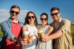 Group of smiling friends with ice cream outdoors. Friendship, leisure and people concept - group of smiling friends with ice cream outdoors in summer royalty free stock photography