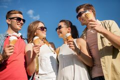 Group of smiling friends with ice cream outdoors. Friendship, leisure and people concept - group of smiling friends with ice cream outdoors in summer royalty free stock image